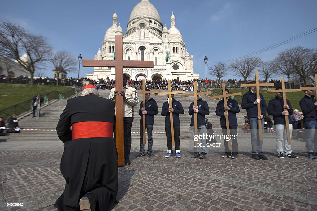 Paris' archbishop Andre Vingt-Trois kneels in front of crosses as he takes part in a Way of the Cross in Paris, in front of the Sacre-Coeur Basilica in Montmartre district, on March 29, 2013, to celebrate Good Friday.