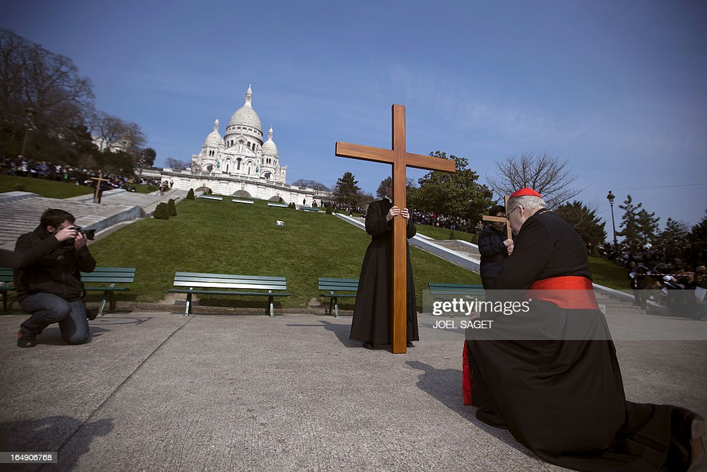 Paris' archbishop Andre Vingt-Trois kneels in front of crosses as he takes part in a Way of the Cross in Paris, in front of the Sacre-Coeur Basilica in Montmartre district, on March 29, 2013, to celebrate Good Friday. AFP PHOTO/ JOEL SAGET