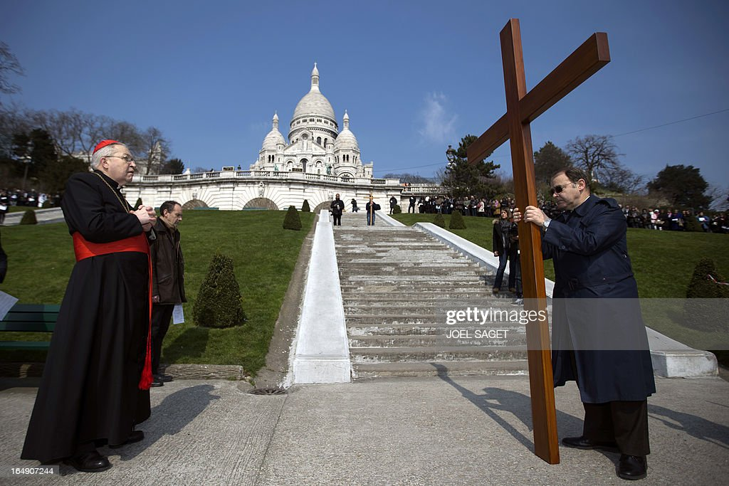 Paris' archbishop Andre Vingt-Trois stands prays in front of a cross, in front of the Sacre-Coeur Basilica in Montmartre district, in Paris, on March 29, 2013, as he takes part in a Way of the Cross to celebrate Good Friday.
