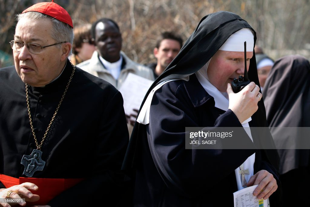 Paris' archbishop Andre Vingt-Trois walks past a nun talking on a walkie-talkie as he takes part in a Way of the Cross to celebrate Good Friday, in front of the Sacre-Coeur Basilica in Montmartre district, in Paris, on March 29, 2013.