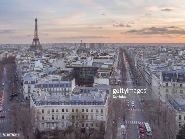 Paris cityscape clad in pink at dusk. Aerial view of Paris and its famous monuments and sites such as Eiffel Tower, Champ de Mars, Grand Palais, Trocadero, Palais de Chaillot, and La Defense.