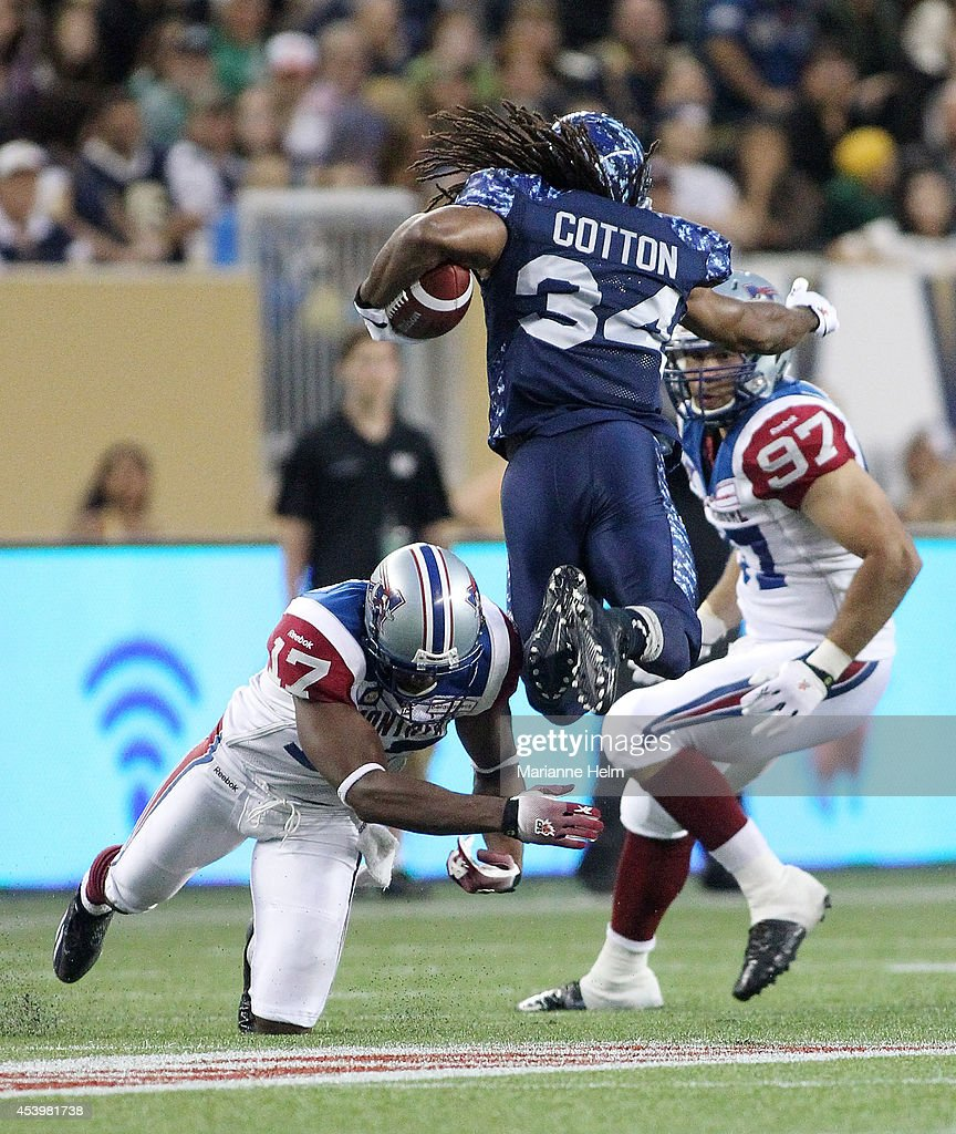 Paris Cotton #34 of the Winnipeg Blue Bombers gets some air as he tries to get past Billy Parker #17 of the Montreal Alouettes in second quarter action in a CFL game at Investors Group Field on August 22, 2014 in Winnipeg, Manitoba, Canada.