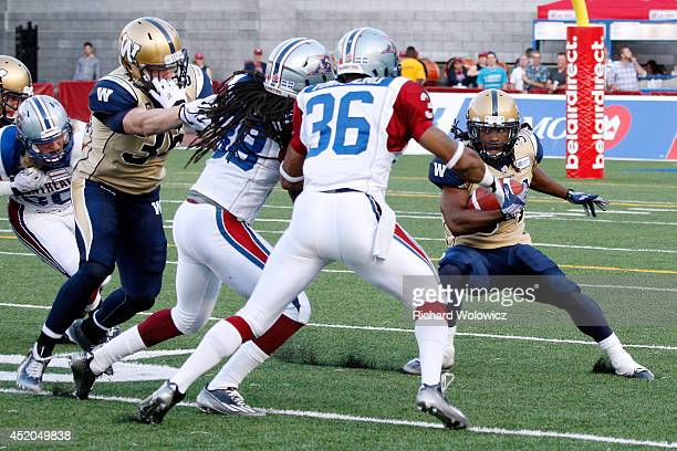 Paris Cotton of the Winnipeg Blue Bombers rushes with the ball in front of Dominique Ellis and Daryl Townsend of the Montreal Alouettes during the...