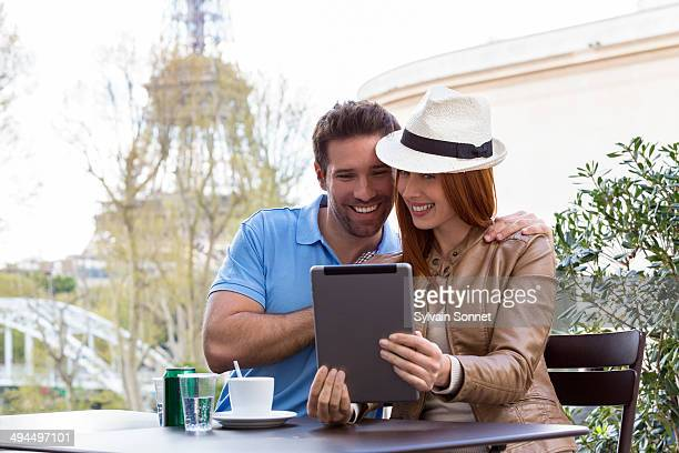 Paris, Couple using Digital Tablet at Cafe