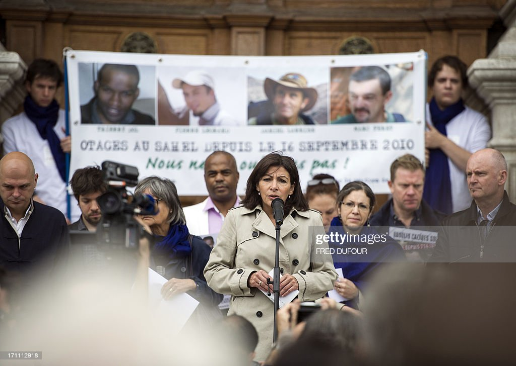 Paris' deputy mayor and socialist candidate to the 2014 municipal elections in Paris Anne Hidalgo (C) speaks next to her campaign team and mayor of Paris' 4th district, Christophe Girard (R) in front of the Paris City Hall during a gathering in support of the four French hostages kidnapped in 2010 in the northern Niger town of Arlit to mark their 1000-day captivity on June 22, 2013. The four French nationals -- Pierre Legrand, Daniel Larribe, Thierry Dol and Marc Feret -- were kidnapped on September 16, 2010, by Al-Qaeda in the Islamic Maghreb (AQIM) from the uranium mining town of Arlit, while working for Satom, a subsidiary of the French nuclear group Areva. Sign reads: ''Let's them regain freedom, Pierre Legrand, Marc Feret, Thierry Dolm Daniel Larribe, hostages in Sahel since September 16, 2010''.