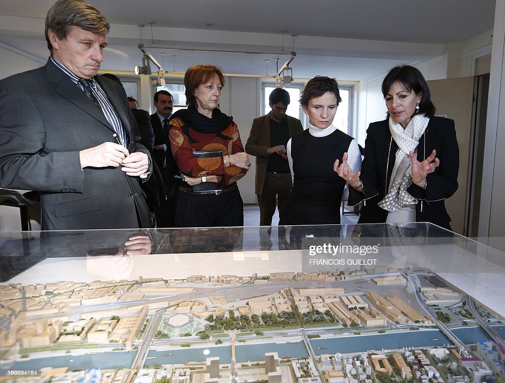 Paris' deputy Mayor and socialist party candidate for the 2014 municipal elections, Anne Hidalgo (R) shows a model of building projects to Carolina Toha (2ndR), mayor of Santiago in Chile, during their joint visit to the 'Paris Rive Gauche' construction project site on January 30, 2013 in Paris.
