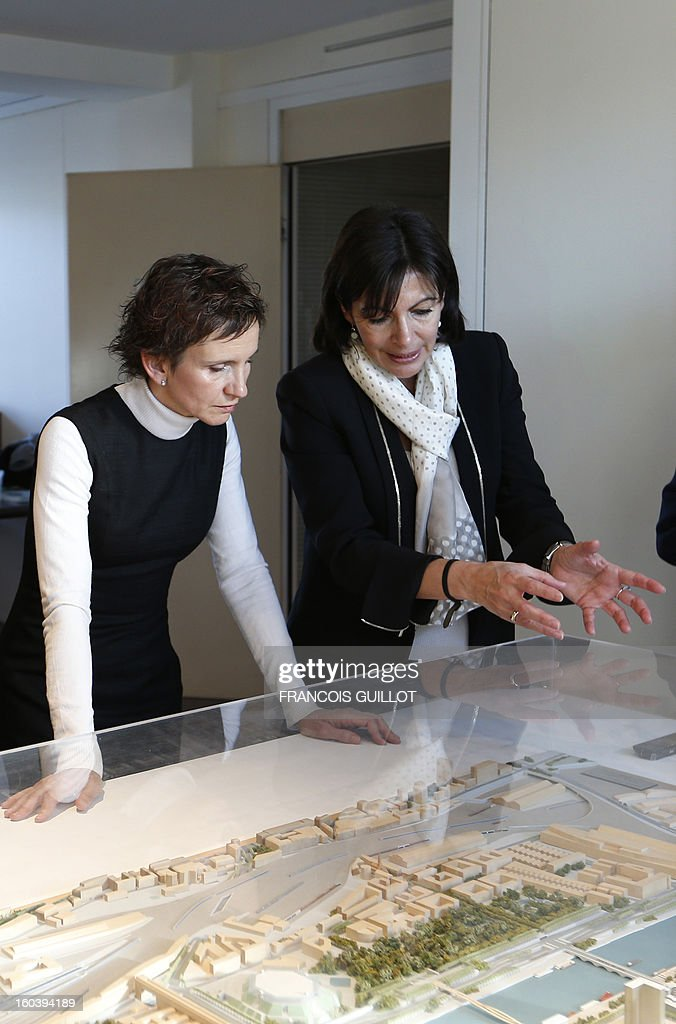 Paris' deputy Mayor and socialist party candidate for the 2014 municipal elections, Anne Hidalgo (R) shows a model of building projects to Carolina Toha, mayor of Santiago in Chile, during their joint visit to the 'Paris Rive Gauche' construction project site on January 30, 2013 in Paris.
