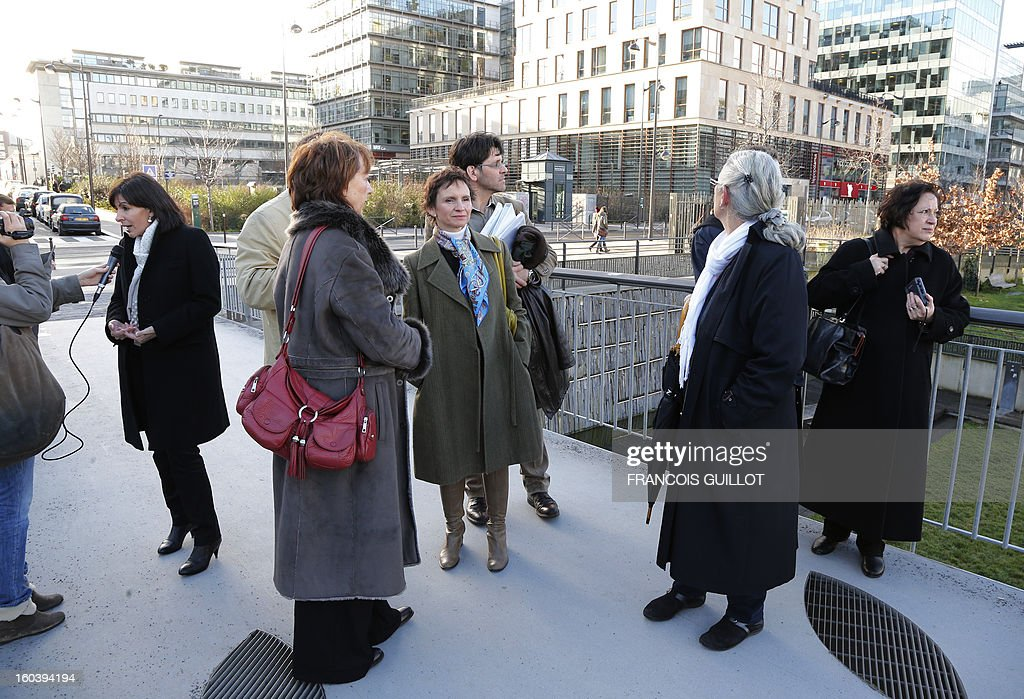 Paris' deputy Mayor and socialist party candidate for the 2014 municipal elections, Anne Hidalgo (L) answers the media while Carolina Toha (C), mayor of Santiago in Chile, looks on during their joint visit to the 'Paris Rive Gauche' construction project site, on January 30, 2013 in Paris.