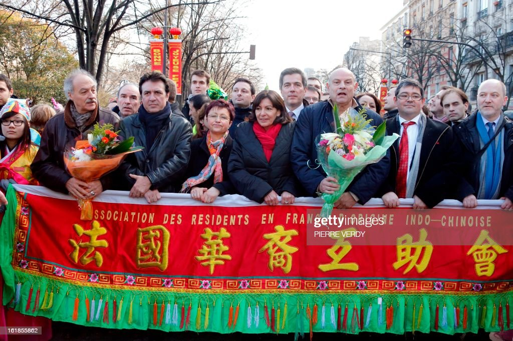 Paris' deputy Mayor and socialist party candidate for the 2014 municipal elections, Anne Hidalgo (C), flanked by French socialist MP Jean-Marie Le Guen (C, R) take part in a parade on February 17, 2013 in Paris as part of the Chinese New Year celebrations. At left is seen Europe-Ecology-Greens party (EELV) councellor of Paris, Yves Contassot and at right, EELV MP Denis Baupin.