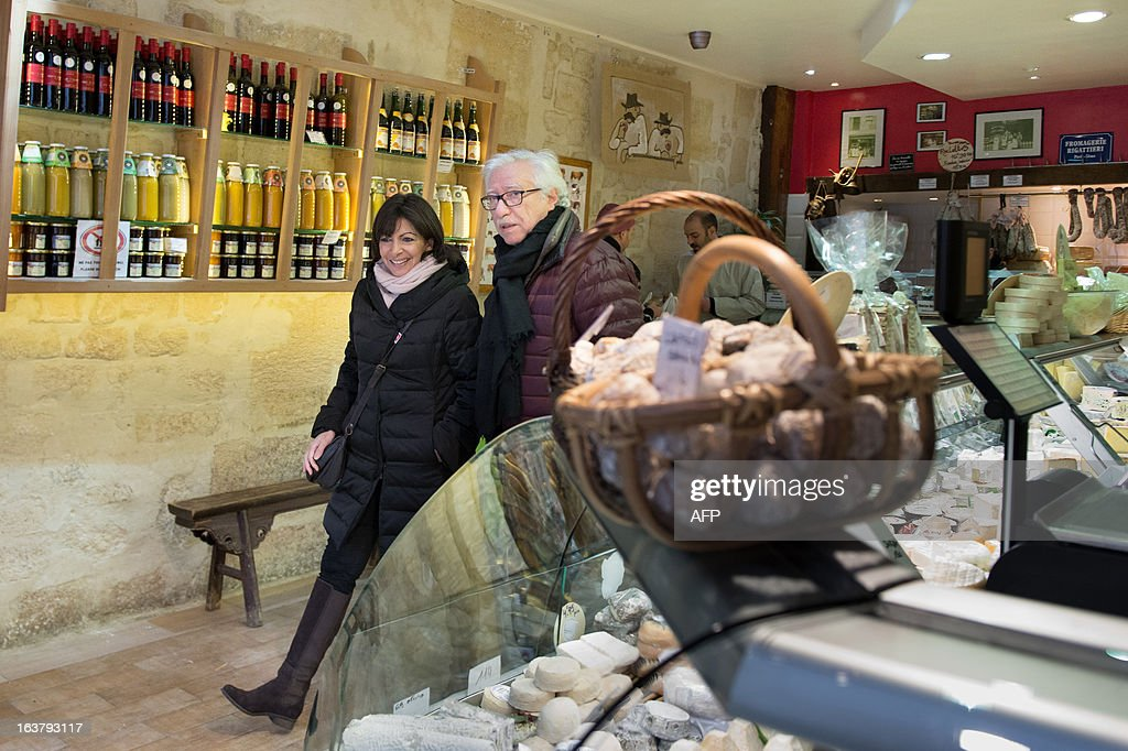 Paris Deputy Mayor and socialist party candidate in the 2014 municipal elections Anne Hidalgo (L), with Pierre Schapira, deputy mayor of Paris responsable for international relations and the French-speaking world, visits a neighbourhood cheese shop as part of her campaign in Paris on March 16, 2013. AFP PHOTO / BERTRAND LANGLOIS