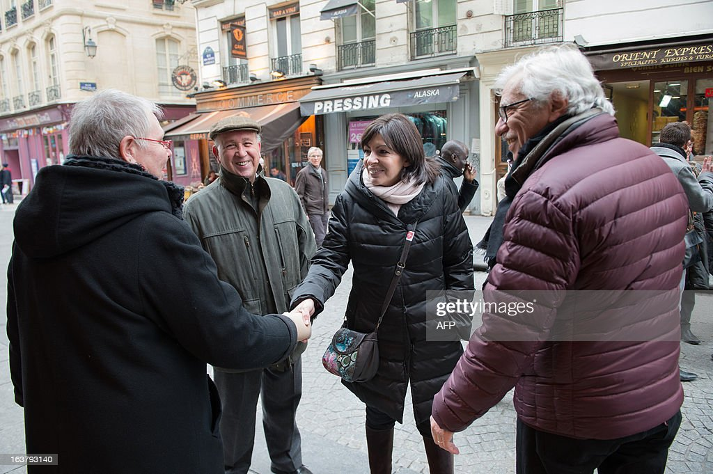Paris Deputy Mayor and socialist party candidate in the 2014 municipal elections Anne Hidalgo (C), with Pierre Schapira (R), deputy mayor of Paris responsable for international relations and the French-speaking world, greets locals as part of her campaign in Paris on March 16, 2013. AFP PHOTO / BERTRAND LANGLOIS