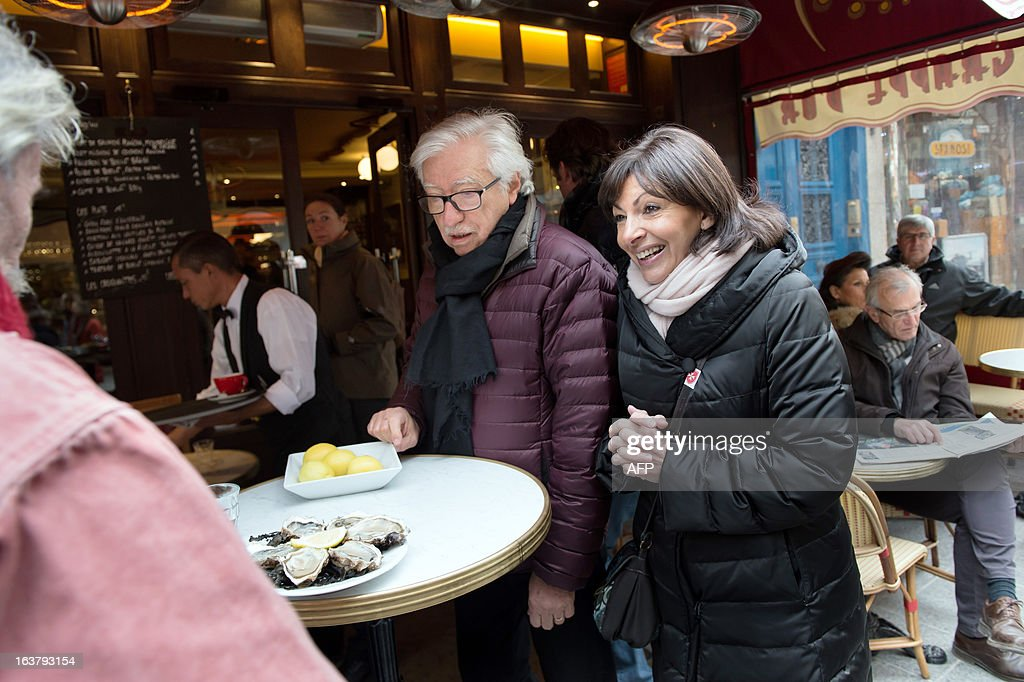 Paris Deputy Mayor and socialist party candidate in the 2014 municipal elections Anne Hidalgo (R), with Pierre Schapira (C), deputy mayor of Paris responsable for international relations and the French-speaking world, visits a neighbourhood chees shop as part of her campaign in Paris on March 16, 2013.
