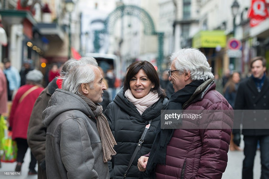 Paris Deputy Mayor and socialist party candidate in the 2014 municipal elections Anne Hidalgo (C), with Pierre Schapira (R), deputy mayor of Paris responsable for international relations and the French-speaking world, visits a neighbourhood in Paris as part of her campaign on March 16, 2013.
