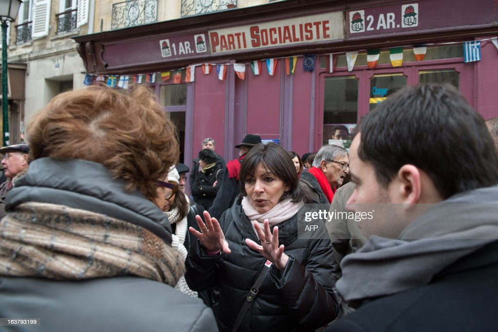 Paris Deputy Mayor and socialist party candidate in the 2014 municipal elections Anne Hidalgo (C) speaks with locals on a visit to a neighbourhood in Paris as part of her campaign on March 16, 2013. AFP PHOTO / BERTRAND LANGLOIS
