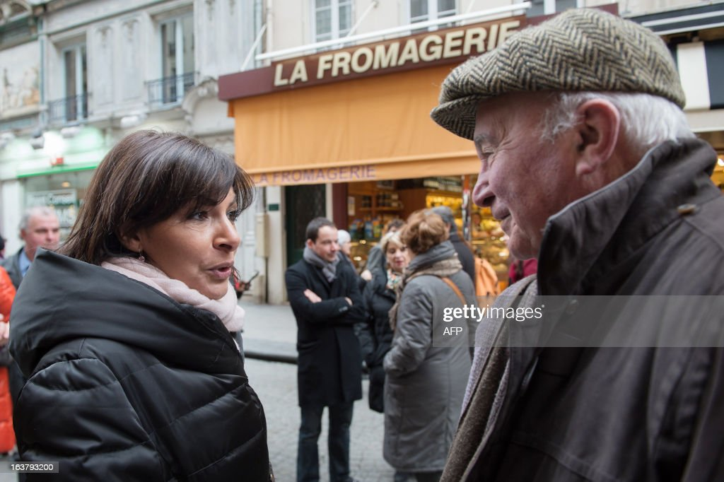 Paris Deputy Mayor and socialist party candidate in the 2014 municipal elections Anne Hidalgo (L) speaks to a local resident on a visit to a neighbourhood as part of her campaign in Paris on March 16, 2013. AFP PHOTO / BERTRAND LANGLOIS