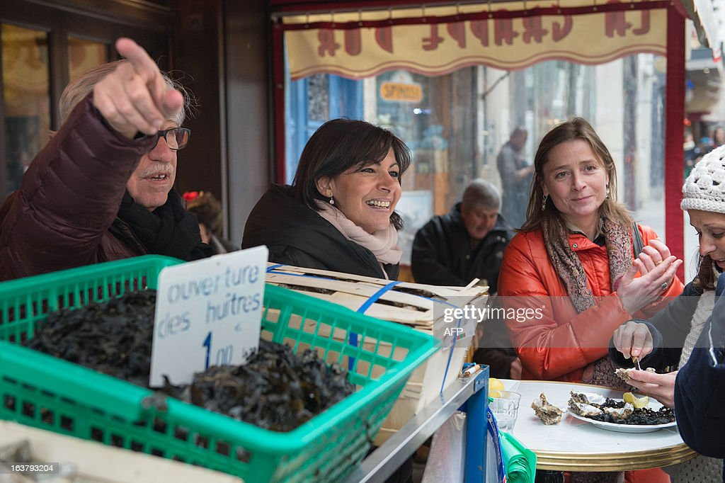 Paris Deputy Mayor and socialist party candidate in the 2014 municipal elections Anne Hidalgo (C), with Pierre Schapira (L), deputy mayor of Paris responsable for international relations and the French-speaking world, visits a neighbourhood restaurant as part of her campaign in Paris on March 16, 2013.