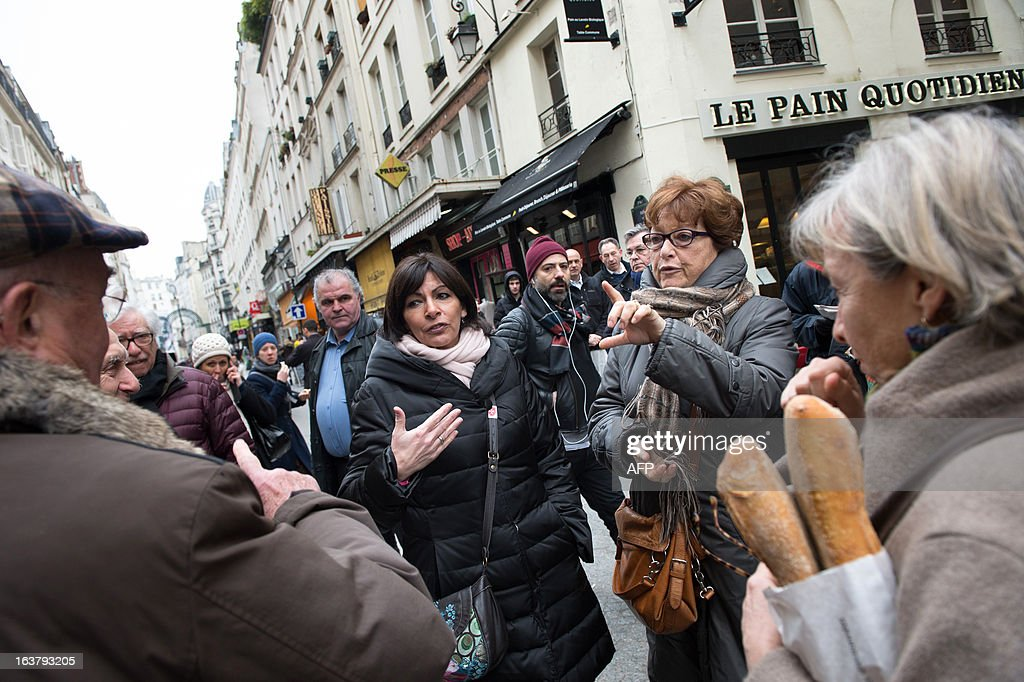 Paris Deputy Mayor and socialist party candidate in the 2014 municipal elections Anne Hidalgo (C) speaks with local residents on a visit to a neighbourhood as part of her campaign in Paris on March 16, 2013. AFP PHOTO / BERTRAND LANGLOIS