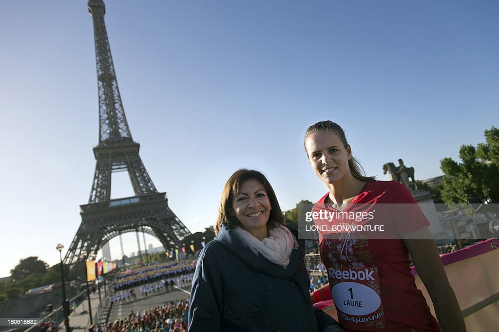 Paris deputy mayor Anne Hidalgo (L)and French swimmer Laure Manaudou pose in front of the Eiffel Tower in Paris on September 15, 2013 before the start of the race 'La Parisienne'.