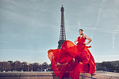 attractive fashion model in Paris in red chiffon dress flying around her, Eiffel Tower in background.
