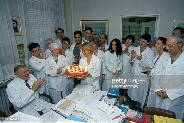 Paris France French cardiologist Christian Cabrol being offered a birthday cake by his staff