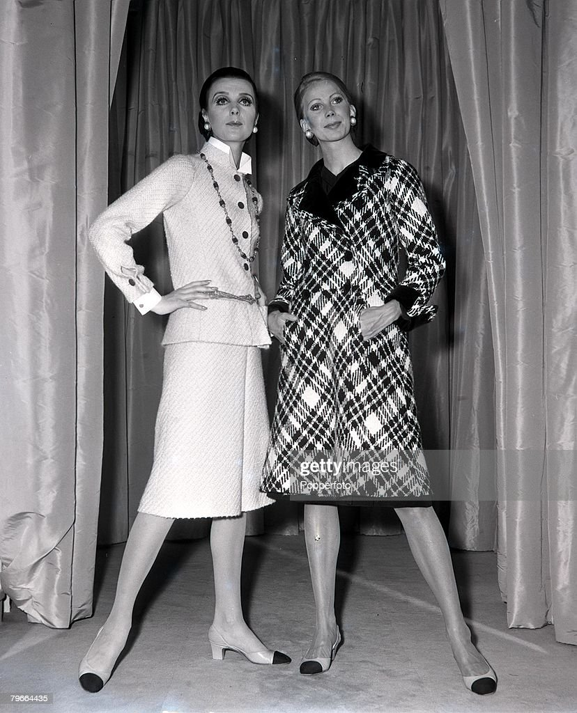 Paris, France, 21st July 1970, Models display a beige tweed skirt suit (left) and plaid grey coat (right) by French designer Coco Chanel being modelled in Paris