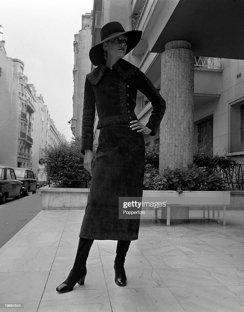 Paris, France, 28th August 1970, A model displays a mid calf suit of brown suede with steel rivets at hem, waist, collar and sleeves by French designer Yves St, Laurent in a Paris street