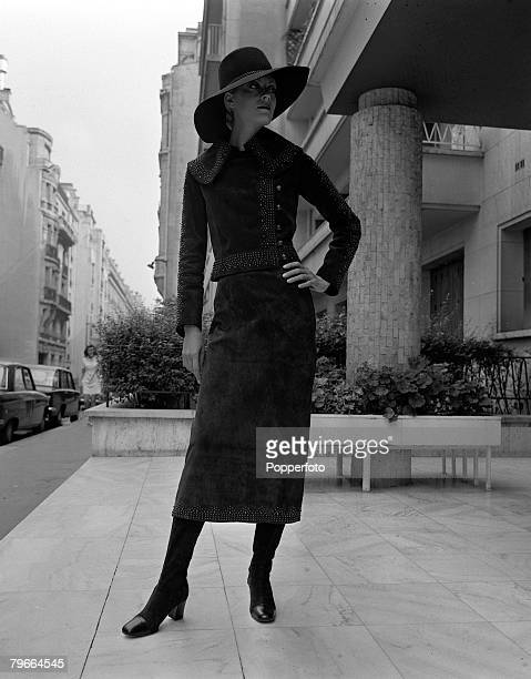 Paris France 28th August 1970 A model displays a mid calf suit of brown suede with steel rivets at hem waist collar and sleeves by French designer...