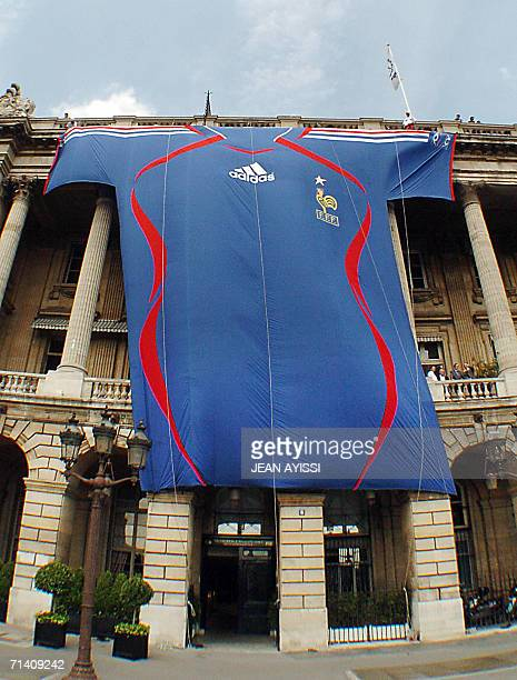 A giant French football jersey is displayed on the facade of the Crillon hotel where the French football team returning from Berlin meets from a...