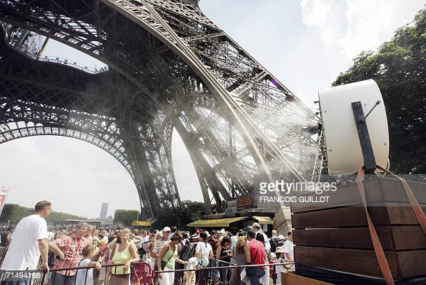 A giant spray refreshes people queueing to visit the Eiffel tower 21 July 2006 in the capital as temperatures in Paris soar to 36 degrees Celsius as...
