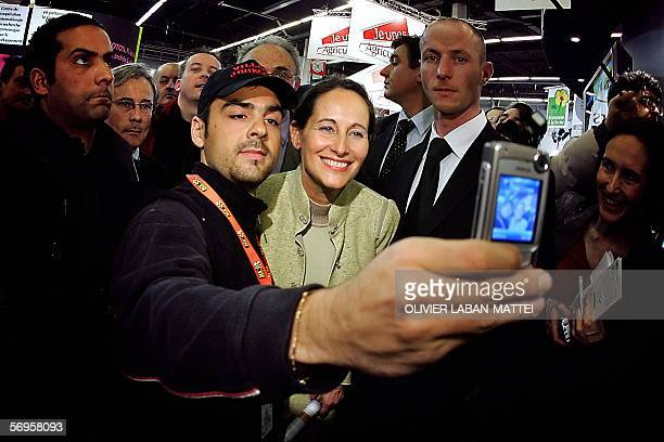 A man takes a picture with French president of Poitou center France regional council and partner of Socialist leader Francois Hollande Segolene Royal...