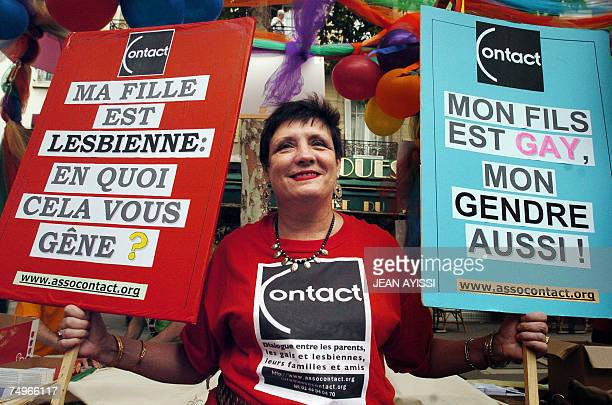 A woman holds placards reading in French 'My daughter is lesbian do you bother' and 'My son is gay my soninlaw as well' during the Gay Pride Parade...