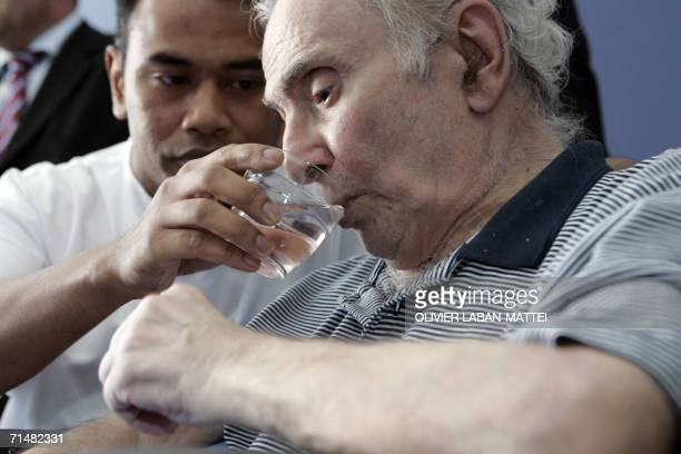 An pensioner is drinking a glass of water in a retirement home 19 July 2006 in Paris as temperatures in Paris soar to 36 degrees Celsius as a...