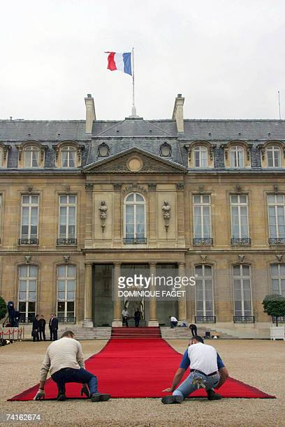 Employees place a red carpet at the entrance of the Elysee Palace 16 May 2007 in Paris before the handover power ceremony between outgoing French...