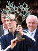 Russia's Nikolay Davydenko celebrates with his trophy with World Judo French Champion David Douillet and French tennis Federation President Christian...