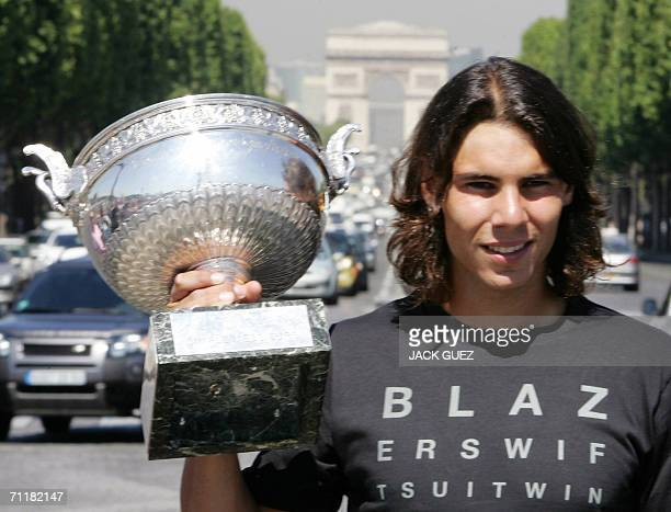 Spanish tennis player Rafael Nadal poses with his trophy 12 June 2006 on the Champs Elysees avenue in Paris a day after his victory in the French...