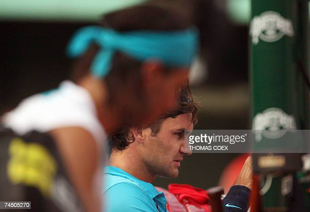 Swiss player Roger Federer and Spanish player Rafael Nadal rest between games during their French Tennis Open final match at Roland Garros 10 June...