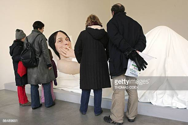 Visitors look at 'In Bed' by Australianborn sculptor Ron Mueck during an exhibition at the Cartier Foundation for Contemporary Art in Paris 27...