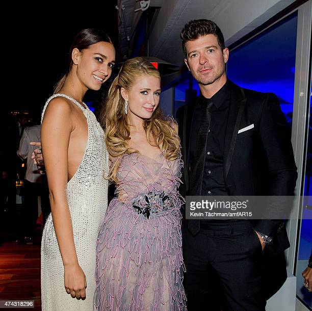 Paris Hilton center and Robin Thicke attend dinner for the amfAR 22nd Annual Cinema Against AIDS Gala at Hotel du CapEdenRoc on May 21 2015 in Cap...