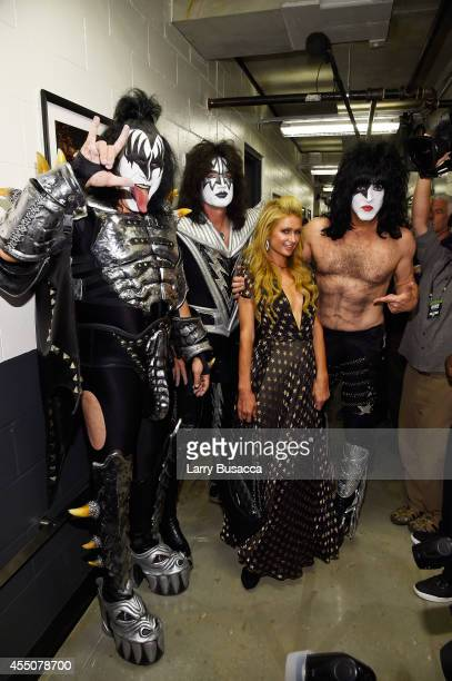 Paris Hilton poses with musicians Gene Simmons Tommy Thayer and Paul Stanley of KISS backstage at Fashion Rocks 2014 presented by Three Lions...