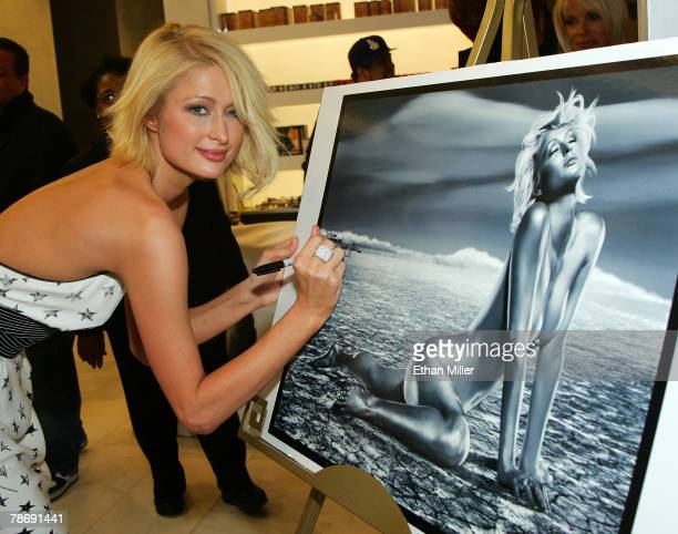Paris Hilton signs a photograph of herself as she attends the grand opening of Color A Salon by Michael Boychuck at Caesars Palace on January 1 2008...