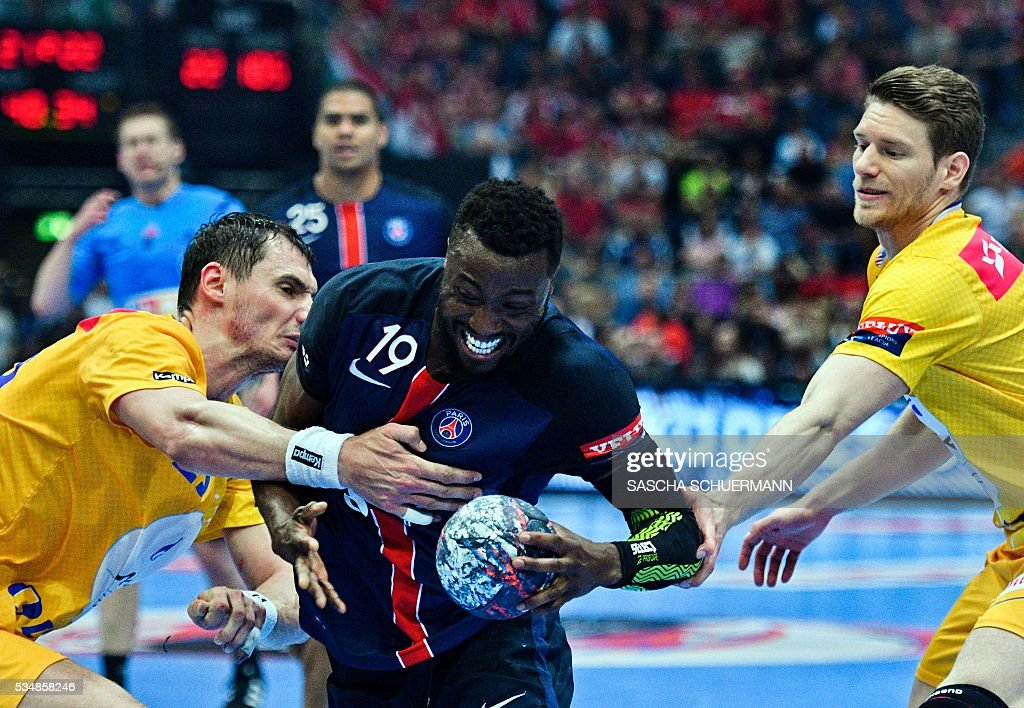 Paris' Luc Abalo vies for the ball with Kielce's players during the Handball EHF Champions League final Four semi final match between KS Vive Tauron Kielce and Paris St-Germain in Cologne, western Germany, on May 28, 2016. / AFP / SASCHA