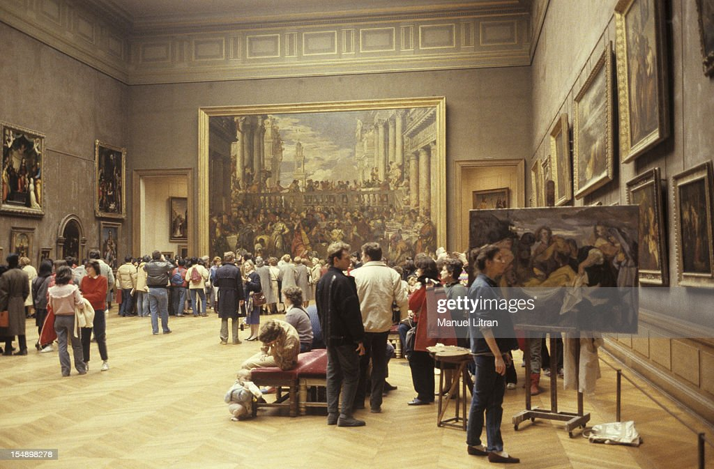 at the bottom of the Salle des Etats, the public admires 'The Wedding at Cana' by Veronese, In the foreground, scribe painted reproduction.