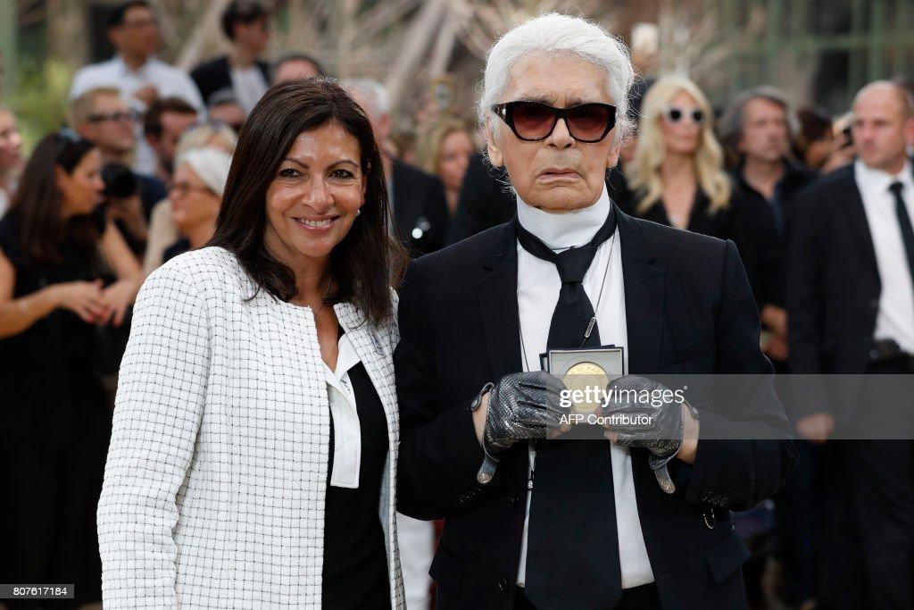 Paris' Mayor Anne Hidalgo awards the Grand Vermeil De La Ville De Paris medal to German fashion designer Karl Lagerfeld after Chanel 2017-2018 fall/winter Haute Couture collection show in Paris on July 4, 2017. / AFP PHOTO / Patrick KOVARIK