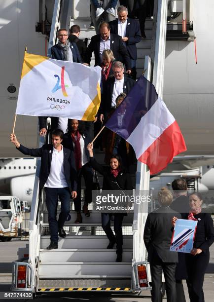 Paris Mayor Anne Hidalgo carries a national flag as she walks with Paris 2024 Bid CoChair Tony Estanguet and others after disembarking from an...
