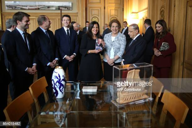 Paris Mayor Anne Hidalgo flanked by French Junior Minister for Economy Benjamin Griveaux holds a copy of Lebanon's President Michel Aoun's book next...