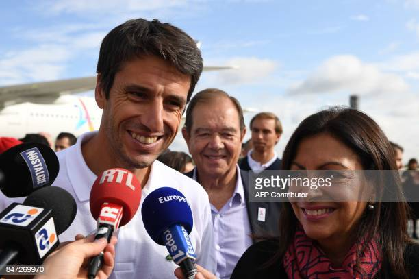 Paris Mayor Anne Hidalgo looks on as Paris 2024 Bid CoChair Tony Estanguet speaks with media representatives after disembarking from an aircraft at...
