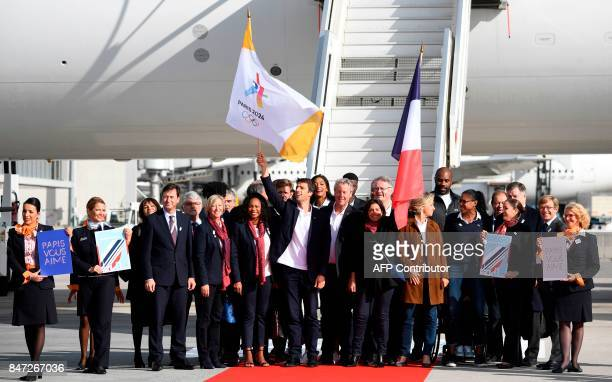 TOPSHOT Paris Mayor Anne Hidalgo waves a national flag as she stands with Paris 2024 Bid CoChair Tony Estanguet IledeFrance regional president...