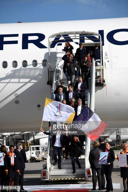 Paris Mayor Anne Hidalgo waves a national flag of France as she disembarks with the Olympic delegation from an aircraft at RoissyCharles de Gaulle...