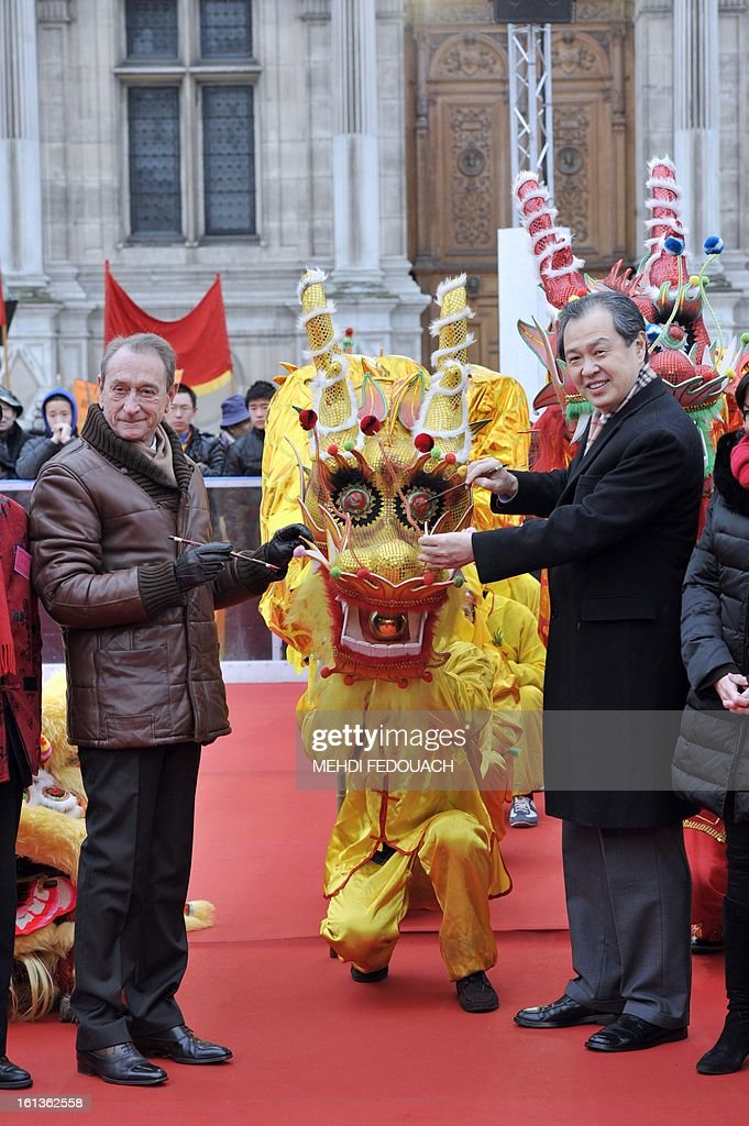 Paris Mayor Bertrand Delanoe (L) and China's ambassador in France Kong Quan traditionally paint the eye of a dragon in front of Paris City Hall during the Chinese New Year celebrations on February 10, 2013 in Paris. Chinese communities world wide traditionally welcomed in the 'Year of the Snake'.