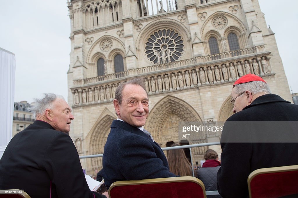 Paris' mayor Bertrand Delanoe (C) looks on next to Patrick Jacquin (L), the head priest and rector of the Notre-Dame de Paris cathedral, and French archbishop Andre Vingt-Trois (R), prior to the ringing of the new bells of Notre Dame Cathedral in Paris on March 23, 2013, as part of the formal inauguration. AFP PHOTO / BERTRAND LANGLOIS